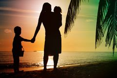 Mother and two kids walking on beach at sunset Stock Photography