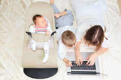 Mother with two kids working from home Stock Image
