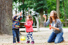 Mother and two little children playing together on playground Royalty Free Stock Photos