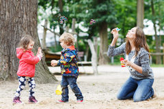 Mother and two little children playing together on playground Stock Photos