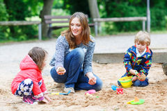 Mother and two little children playing together on playground Stock Images