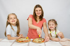 Mother and two little daughters happy sitting at pizzas royalty free stock image