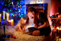 Mother and two little daughters opening a magical Christmas gift. Young mother and her two little daughters opening a magical Christmas gift by a Christmas tree Stock Photography