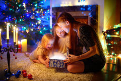 Mother and two little daughters opening a magical Christmas gift. Young mother and her two little daughters opening a magical Christmas gift by a Christmas tree Royalty Free Stock Photos