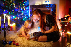 Mother and two little daughters opening a magical Christmas gift. Young mother and her two little daughters opening a magical Christmas gift by a Christmas tree Royalty Free Stock Photo
