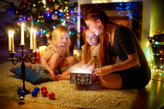 Mother and two little daughters opening a magical Christmas gift stock images