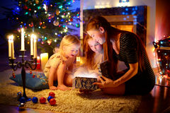 Mother and two little daughters opening a magical Christmas gift. Young mother and her two little daughters opening a magical Christmas gift by a Christmas tree Royalty Free Stock Image