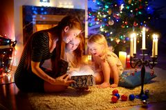 Mother and two little daughters opening a magical Christmas gift. Young mother and her two little daughters opening a magical Christmas gift by a Christmas tree Stock Image