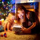Mother and two little daughters opening a magical Christmas gift Stock Photos