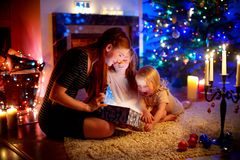 Mother and two little daughters opening a magical Christmas gift. Young mother and her two little daughters opening a magical Christmas gift by a Christmas tree Stock Photo