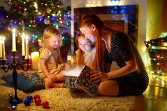 Mother and two little daughters opening a magical Christmas gift. Young mother and her two little daughters opening a magical Christmas gift by a Christmas tree Stock Photos