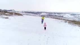 Mother and daughters running to each other. Mother and two little daughters running to each other and hugging outdoors on snow hill stock footage