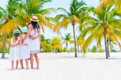 Mother with two little kids on white beach in palm grove Stock Photos