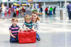 Mother and two little sibling boys at the airport Stock Photos