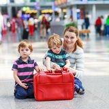 Mother and two little sibling boys at the airport Stock Images