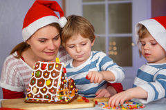 Mother and two little sons preparing a gingerbread cookie house Royalty Free Stock Image
