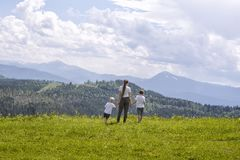Mother and two little sons stand holding hands on a green field against a background of forest, mountains and sky with clouds stock photo