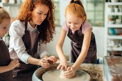 Mother and two redhead daughters made clay cup with pottery wheel Stock Photos