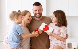 Mother and two smiling kids congratulating dad with Fathers day while standing in kitchen in morning