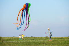 Mother and two sons flying kite together on green field Royalty Free Stock Photography