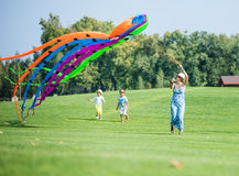 Mother and two sons flying kite together on green field Royalty Free Stock Images