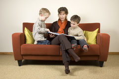 Mother And Two Sons Reading A Book 4 Stock Photography