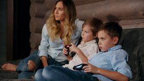 Mother and two sons sitting on the sofa in his house playing video games with wireless joystick. Happy people in the. House stock video footage