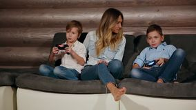 Mother and two sons sitting on the sofa in his house playing video games with wireless joystick. Happy people in the. House stock footage