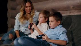 Mother and two sons sitting on the sofa in his house playing video games with wireless joystick. Happy people in the. House stock video