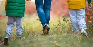 Mother and two sons walking in the autumn Park holding hands.Feet close up. royalty free stock images