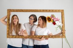 Mother and two twin sisters enjoy in very funny attitude stock photography
