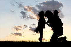 Mother and Two Young Children Hugging and Kissing. The Silhouette of a mother and her two young children; a little boy and his baby brother are playing outside Stock Photo