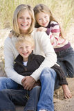 Mother and two young children sitting on beach stock photos