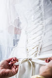Mother Tying the Bride's Wedding dress royalty free stock photography