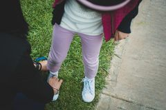 Mother tying child`s shoe laces - Mother`s Day use. royalty free stock photo
