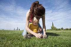 Mother tying her daughter shoes Royalty Free Stock Photos