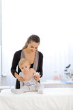 Mother undressing baby at pediatricians cabinet Stock Photography
