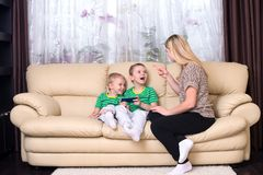 Mother is unhappy that the children play with the phone. stock image
