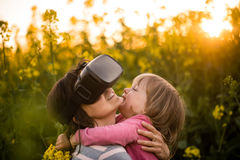 Mother uses head-mounted display in rapeseed field while hugging girl child. Royalty Free Stock Image
