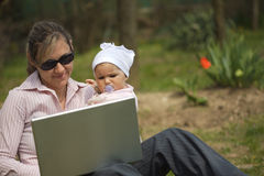 Mother uses a laptop Stock Photos