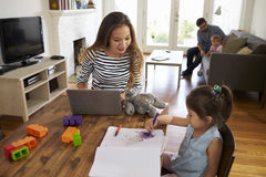 Mother Uses Laptop Whilst Father Plays With Children At Home stock image