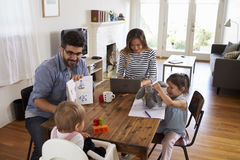 Mother Uses Laptop Whilst Father Plays With Children At Home Royalty Free Stock Images