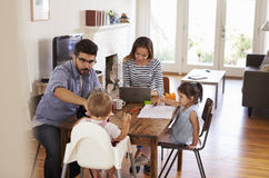 Mother Uses Laptop Whilst Father Plays With Children At Home Royalty Free Stock Photography