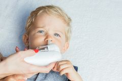 Mom cleaning baby boy nose Royalty Free Stock Photography