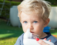 Mom cleaning baby boy nose outdoor Royalty Free Stock Photography