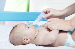 Mother using baby nasal aspirator Royalty Free Stock Photo