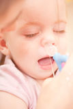 Mother using bulb syringe. To clean unhappy infant baby's nose Stock Image