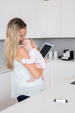 Mother using digital tablet while carrying her baby in kitchen Stock Images