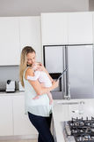 Mother using digital tablet while carrying her baby in kitchen Royalty Free Stock Image