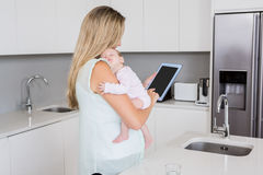 Mother using digital tablet while carrying her baby in kitchen. At home Stock Photography